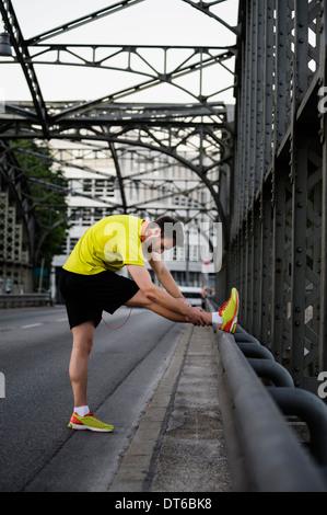 Giovane maschio runner stretching gambe sul ponte Foto Stock