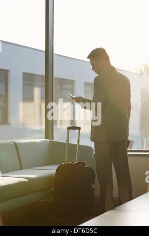 Uomo maturo in aeroporto con telefono cellulare Foto Stock