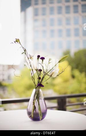 Una tabella su una terrazza in città. Un vaso di fiori. Piccoli fiori viola e giglio bianco e fioriture di orchidee. Foto Stock