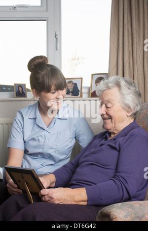Personal care assistant guardando alla fotografia con il senior donna Foto Stock