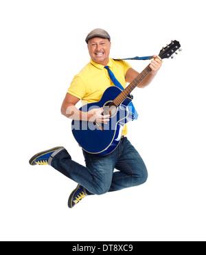 Sorridenti giovane chitarrista jumping con una chitarra acustica in aria isolata su sfondo bianco Foto Stock