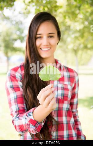 Donna sorridente Holding Leaf Foto Stock