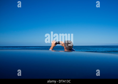 Vista posteriore dell'uomo di prendere una fotografia di vista oceano Foto Stock