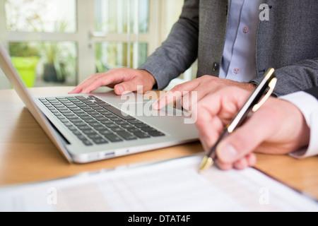 Primo piano delle mani di due imprenditori che lavorano insieme in ufficio con computer portatile Foto Stock