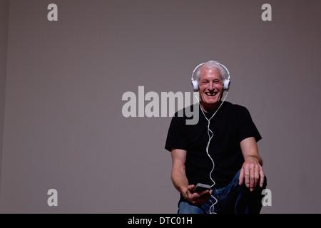 Ritratto di senior uomo che ascolta mp3 player sulle cuffie Foto Stock