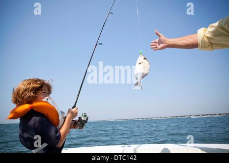 Ragazzo la bobinatura di pesce sulla barca, Falmouth, Massachusetts, STATI UNITI D'AMERICA Foto Stock