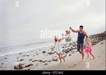 I genitori e i due giovani ragazze camminando sulla spiaggia Foto Stock