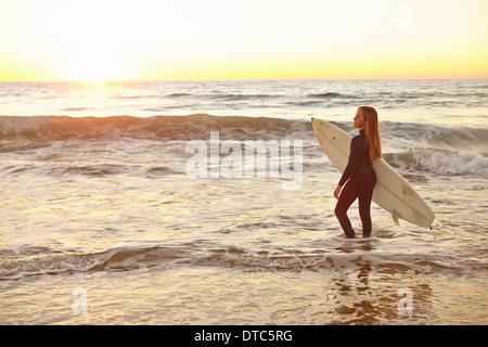 Ragazza che trasportano le tavole da surf in mare muta da indossare Foto Stock