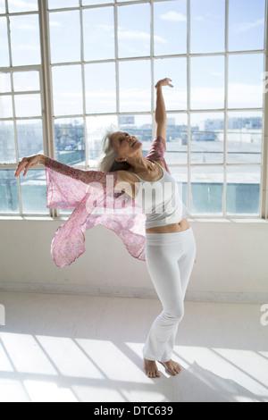 Senior woman dancing in appartamento soleggiato Foto Stock