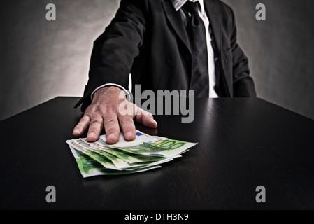 Argomento corruzione: mano spinge le fatture in euro sul tavolo. Foto Stock
