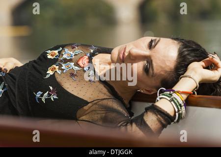 Una donna sdraiata sulla schiena, indossando un top nero con maniche a strapiombo e braccialetti di ricamo sul suo Foto Stock