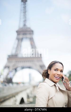 Donna che parla al cellulare dalla Torre Eiffel, Parigi, Francia Foto Stock