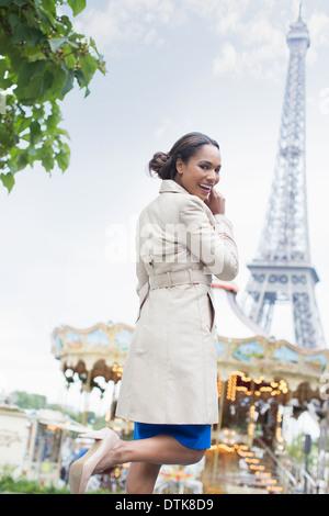 Donna camminare vicino a giostra e Torre Eiffel, Parigi, Francia Foto Stock