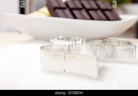 Cookie cutter a forma di cuore sulla farina in background una ciotola con il bianco e il cioccolato fondente Foto Stock