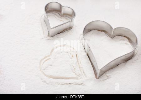 Due cookie cutter a forma di cuore sulla farina bianca Foto Stock
