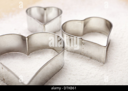 Tre cookie cutter in forma di cuore come vista da vicino sulla farina bianca Foto Stock