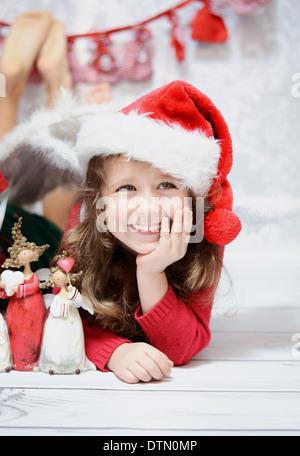 Sorridente e carina ragazza in un cappello da Babbo Natale Foto Stock