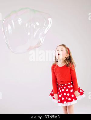 Poco carino ragazza rendendo le bolle di sapone Foto Stock