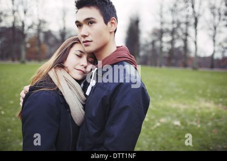 Affettuosa giovane adolescente abbracciando all'esterno. Giovane uomo e donna in amore nel parco. Copyspace. Foto Stock