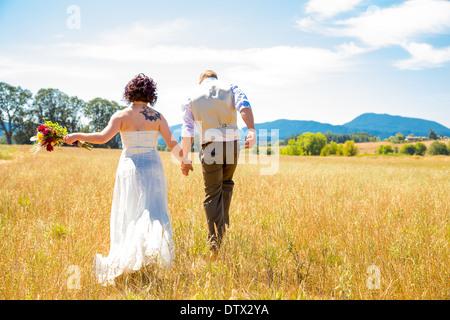 Sposa e lo sposo camminare insieme il giorno delle nozze attraverso un campo in Oregon. Foto Stock