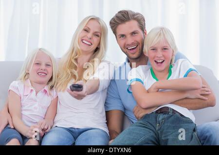 La famiglia felice seduta sul lettino Foto Stock