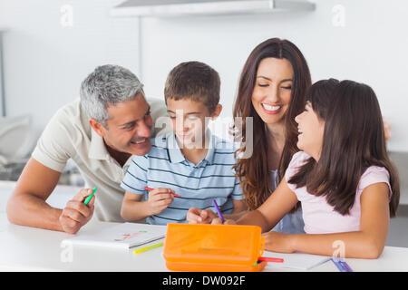 Famiglia sorridente disegno insieme in cucina Foto Stock