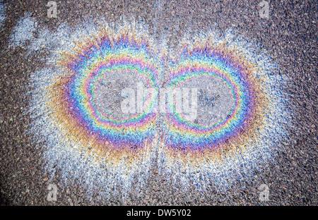Macchie di olio sul bagnato su strada asfaltata formando rainbow modelli di interferenza Foto Stock