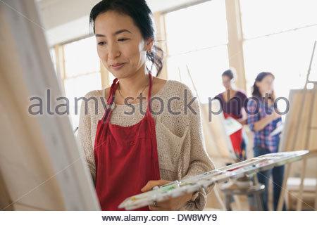 Donna pittura in classe d'arte Foto Stock