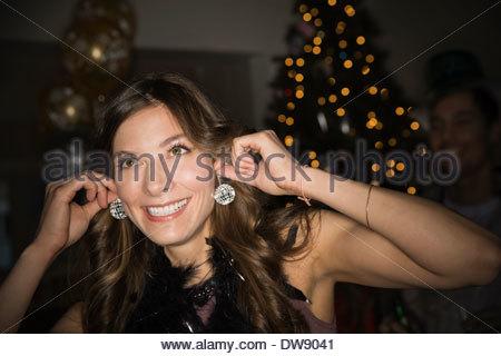 Donna che utilizza una mini discoteca palle come orecchini durante il cenone di capodanno con ballo Foto Stock