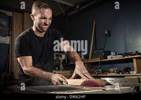 Falegname maschio utilizzando una sega rotante in officina