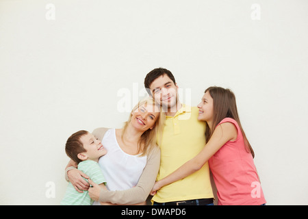 Ritratto di affettuosa famiglia di quattro persone che posano su sfondo bianco Foto Stock