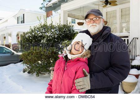 Nonno e nipote al di fuori di casa in inverno Foto Stock