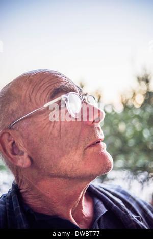 Ritratto di senior uomo che guarda verso l'alto Foto Stock