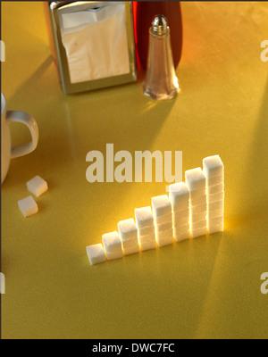Pila di cubetti di zucchero in forma di grafico su una tabella di colore giallo Foto Stock