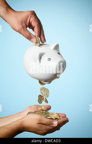 Mettendo mano moneta nel salvadanaio e monete che fluisce fuori Foto Stock