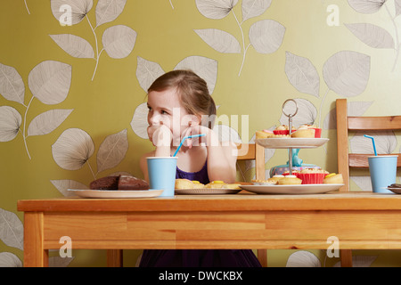 Annoiato cerca ragazza a tavola con piatti per le feste Foto Stock