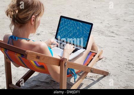 Donna al lavoro su computer portatile sulla spiaggia Foto Stock