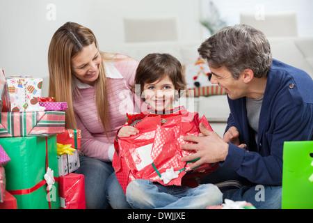 Ragazzo e genitori apertura Regalo di natale Foto Stock