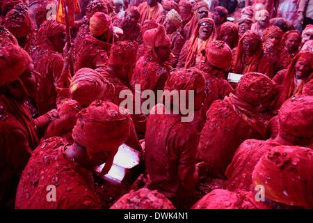 Barsana, India. 8 Mar 2014. In una vecchia tradizione gli uomini dal vicino villaggio di Nandgaon sedersi e faccia Foto Stock