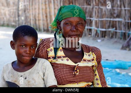 Madre e figlia ubicazione sotto il Mango Tree mentre il fissaggio della rete da pesca a Quirimbas National Park, Foto Stock