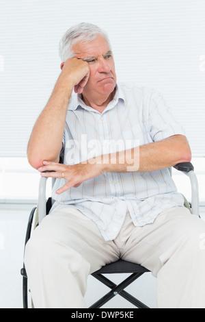 Triste senior uomo seduto nella sedia a rotelle Foto Stock