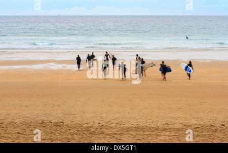 Gruppo di surfisti in motion blur camminando sulla spiaggia al tramonto Foto Stock