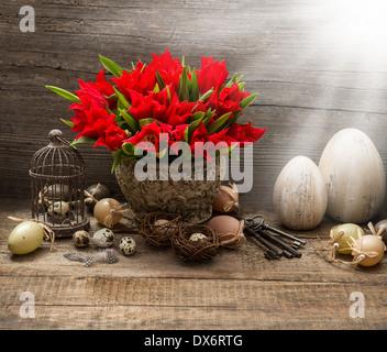 Vintage composizione di pasqua con uova e tulipani rossi. nostalgico still life home interno con fasci di luce Foto Stock