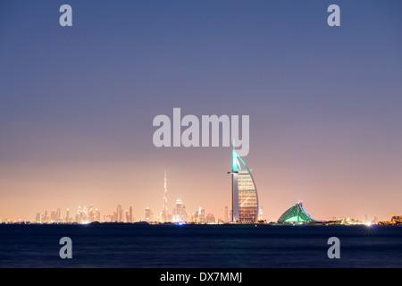 Lo skyline di notte in mare di lusso al Burj al Arab hotel e la città di Dubai con il Burj Khalifa Tower in distanza Foto Stock