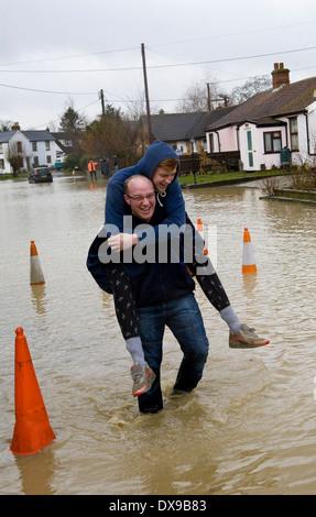 Residenti lottano attraverso il villaggio inondato di Steeple Bumpstead in Essex oggi dopo dopo la pioggia caduta Foto Stock