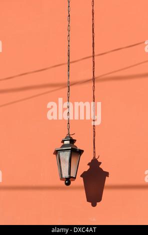 Una lampada elettrica si blocca su una catena contro un rosa salmone parete. Antigua Guatemala, Repubblica del Guatemala. Foto Stock