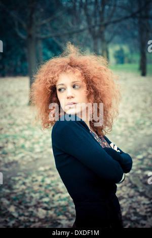 Giovane bella rossa di capelli ricci donna presso il parco Foto Stock