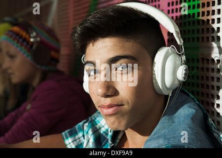Close-up ritratto di ragazzo seduto accanto alla parete esterni, indossa le cuffie e guardando la telecamera, Germania