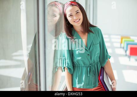 Ritratto di casual imprenditrice appoggiata contro la finestra nel sole ufficio Foto Stock