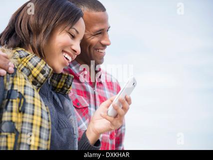 Felice coppia tramite telefono cellulare all'aperto Foto Stock